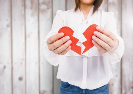 Mid-section of woman holding a broken heart against wooden background