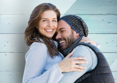 cuddling: Happy couple embracing each other against wooden background