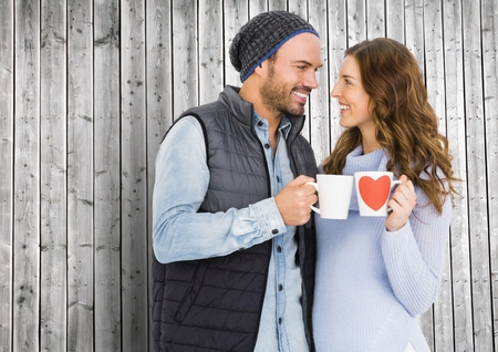 drink coffee: Romantic couple holding mug against wooden background Stock Photo
