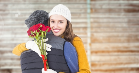 Couple with rosses embracing each other against wooden background Stock Photo