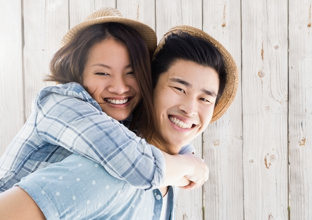 piggyback: Portrait of man giving piggy back to woman against wooden background