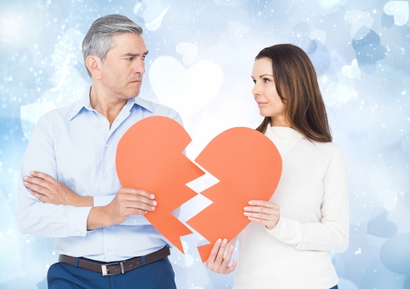 Mature couple holding a broken heart against bokeh Stock Photo
