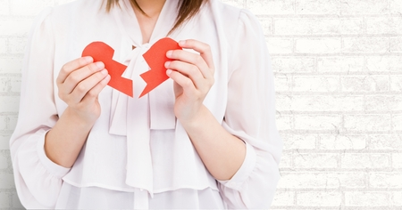 Mid-section of woman holding two broken hearts against brick wall