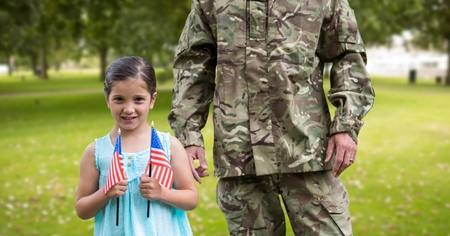 Portrait of girl holding american flag in park