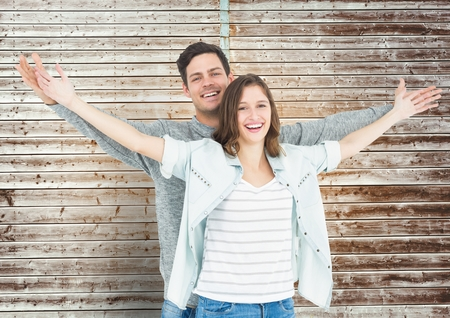 Portrait of happy couple standing with arms outstretched against wooden background Stock Photo