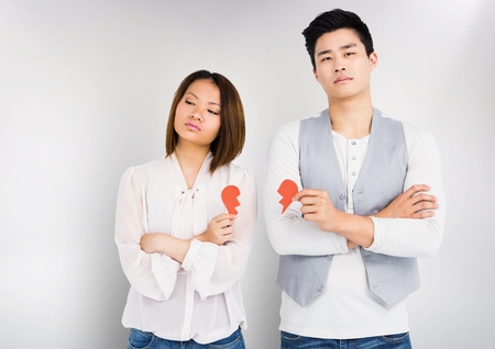 annoying: Sad couple holding broken hearts against white background Stock Photo