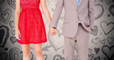 couple holding hands: VMid-section of couple holding hands against digitally generated heart background Stock Photo