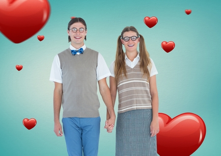 couple holding hands: Portrait of nerd couple holding hands against digitally generated heart background Stock Photo