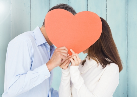 flooring: Romantic couple hiding their face behind heart against wooden background Stock Photo