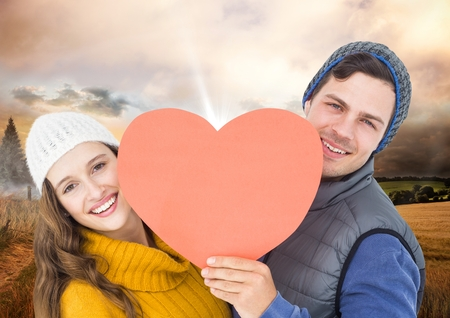 Portrait of romantic couple holding heart against digitally composite field background