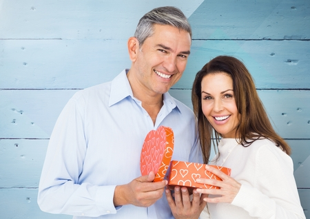 fondness: Portrait of smiling couple standing with gift box against wooden background