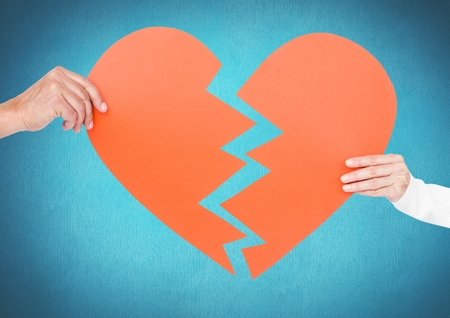 Hands of couple holding broken heart against blue background