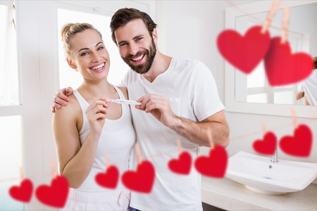 Portrait of happy couple holding pregnancy test in bathroom at home Stock Photo