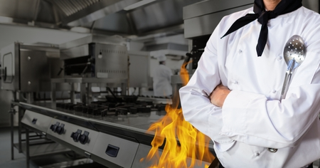 kitchen equipment: Mid section of chef standing with arms crossed in kitchen of restaurant