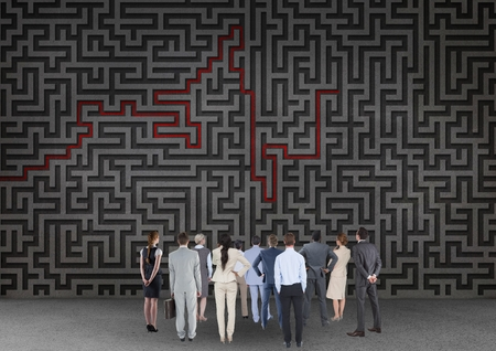 Digital composite image of businesspeople looking over maze Stock Photo
