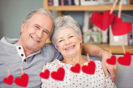 Composite image of red heart and happy senior couple embracing each other