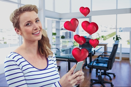 Portrait of beautiful woman using mobile phone with digitally generated hearts in office