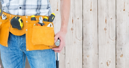 tool belt: Mid section of handyman with tool belt around his waist against wooden background