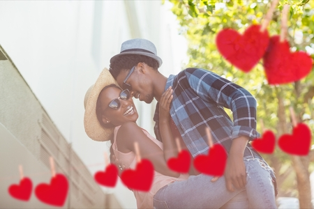 Composite image of red hanging hearts and affectionate couple embracing each other