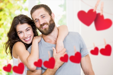 Composite image of couple embracing at home with hanging hearts around Stock Photo