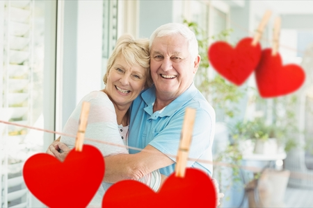 Portrait of smiling senior couple embracing each other against hearts hanging on line Stock Photo