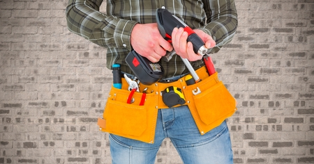 tool belt: Mid section of handy man with tools and drill against brick background