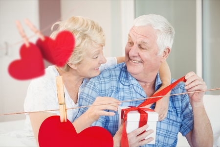 Composite image of hanging hearts and senior couple opening a gift box at home Stock Photo
