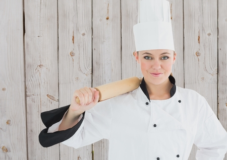 nudelholz: Portrait of smiling female chef holding rolling pin against wooden background Lizenzfreie Bilder
