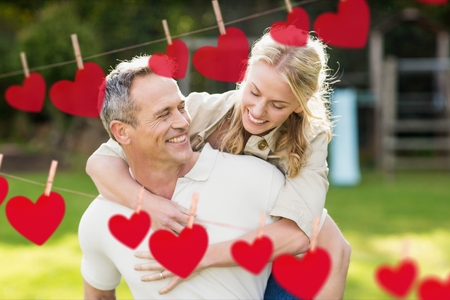 Composite image of red hanging heart and smiling man giving a piggyback to woman Stock Photo