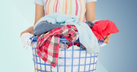 Mid section of female cleaner holding laundry against blue background Stock Photo