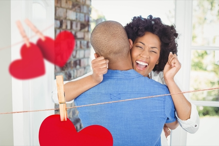 Composite image of red hanging hearts and excited couple embracing at home