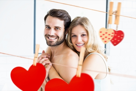 Composite image of romantic couple embracing with red hearts hanging on line Stock Photo