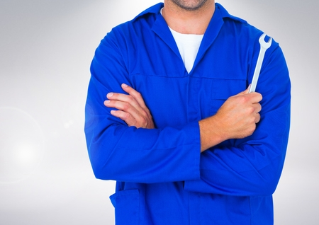 Mid section of mechanic holding a wrench against white background