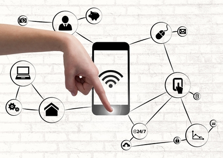 Composite image of hand using a smartphone with application icons Stock Photo