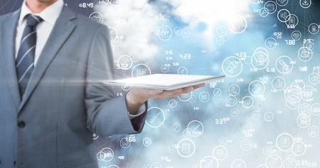 smolder: Mid section of businessman holding digital tablet digitally generated background
