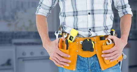 Mid-section of handy man with tool belt against blur background