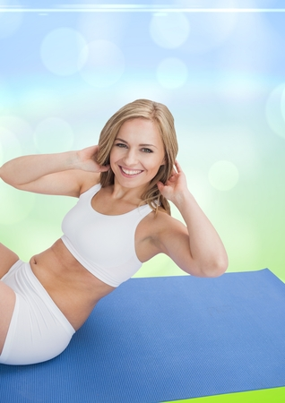 working attire: Beautiful woman performing yoga on blue mat against bokeh background Stock Photo