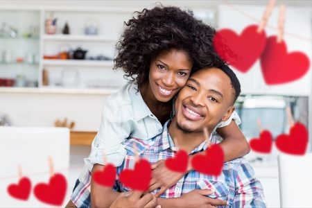 Composite image of red hanging heart and happy couple embracing each other in living room