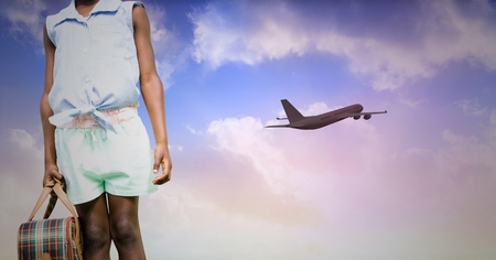 mid distance: Mid section of female tourist with airplane at distance in the sky