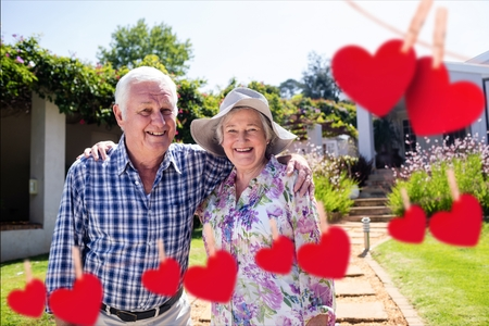 Composite image of red hanging heart and happy senior couple standing with arm around in park