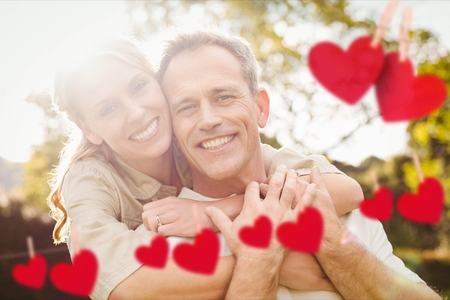 Composite image of red hanging heart and happy couple embracing each other in park Stock Photo