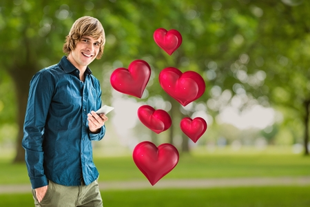 Portrait of smiling man holding mobile phone against digitally generated red hearts Stock Photo
