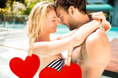 Romantic couple embracing each other near poolside against hearts hanging on a line