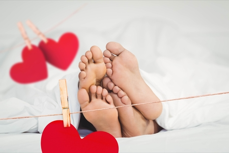 Composite image of red hanging hearts and couple lying on bed in bedroom Stock Photo