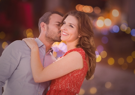 Man kissing woman on cheeks against bokeh background