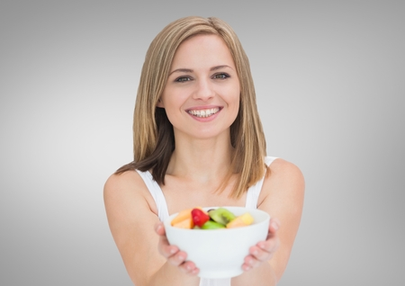 Portrait of beautiful woman holding fruit bowl against grey background
