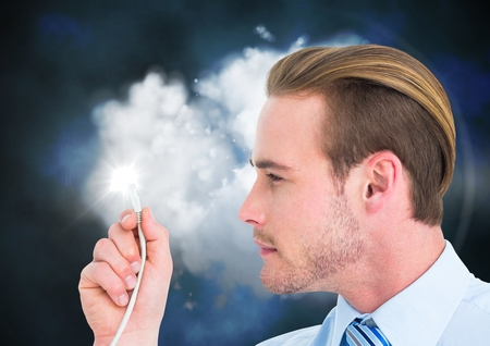 Businessman looking at cable with flare against digitally generated background Stock Photo