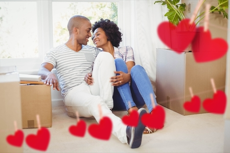 Romantic couple embracing in living room at home against hearts hanging on a line