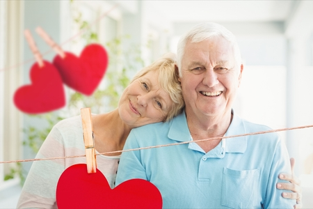 Composite image of happy senior couple together with red hearts hanging on line Stock Photo