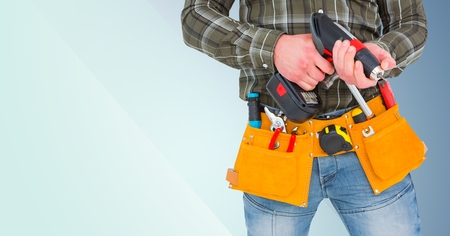 Mid section of handyman holding drill machine and plank against blue background Stock Photo